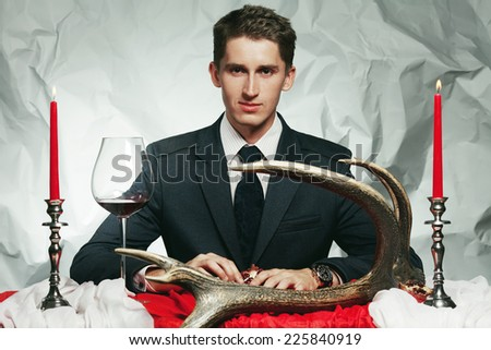 Baroque dinner of blue blood aristocrat. Handsome man eating fresh meat at vintage restaurant. Baroque accessories: deer horn, red & white table sheet. Expensive watch. Retro style. Indoor shot - stock photo