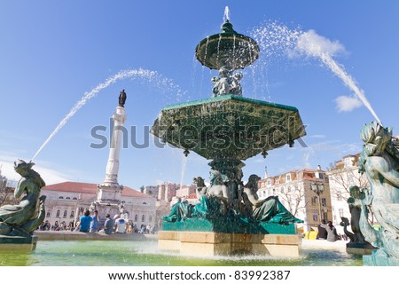 Baroque fountain on rossio square the liveliest placa in Lisbon with wavy cobble stone pattern, Portugal