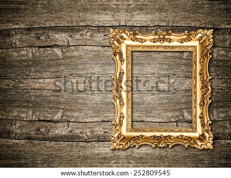 Baroque golden frame over rustic wooden background. Grungy texture - stock photo