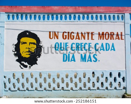 BARRACOA, CUBA - NOVEMBER 25: portrait of Che Guevara near a slogan written on a wall of the town, on november 25, 2014, in Barracoa, Cuba. - stock photo