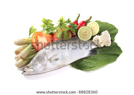 Barramundi or asian seabass fish with tomatoes, key lime, chilies, lemongrass, salad and ice. - stock photo