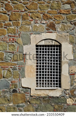 barred window in the stone wall