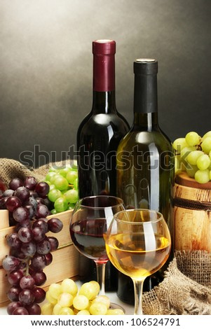 barrel, bottles and glasses of wine and ripe grapes on grey background