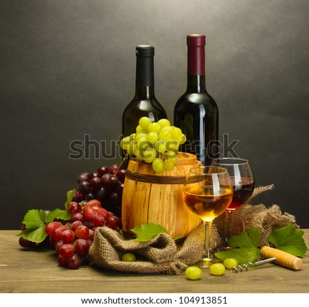 barrel, bottles and glasses of wine and ripe grapes on wooden table on grey background - stock photo