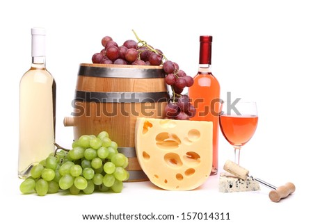 Barrel cheeses bottles and glasses of wine and ripe grapes - stock photo