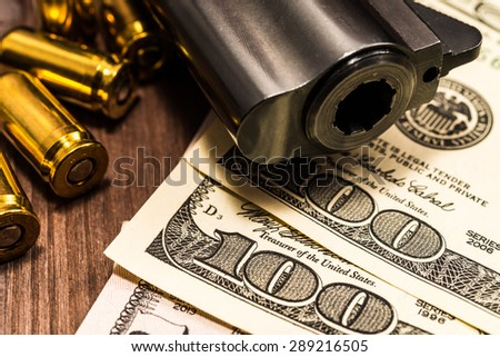 Barrel of a revolver with cartridges and money on the wooden table. Close up view - stock photo