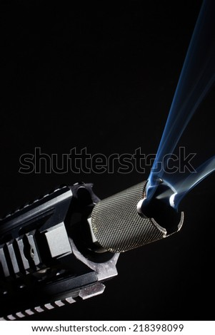 Barrel of a rifle that has smoke coming out - stock photo