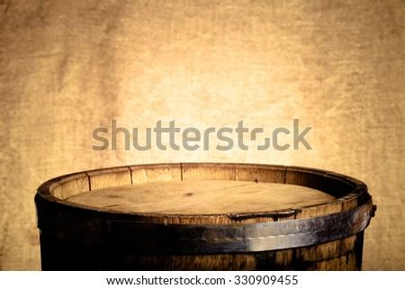 Barrel of wine on burlap background. Toned. - stock photo