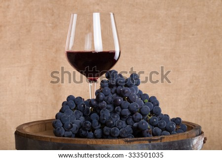 Barrel, wineglass with some red wine and ripe grapes of wine on burlap background. - stock photo
