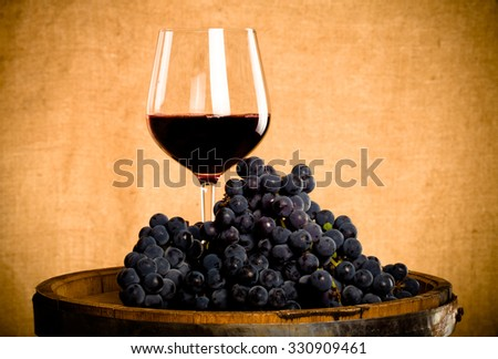 Barrel, wineglass with some red wine and ripe grapes of wine on burlap background. Toned. - stock photo