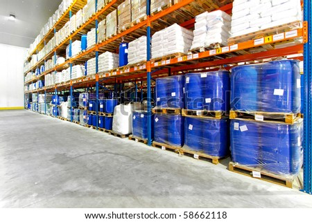 Barrels and boxes in big industrial warehouse