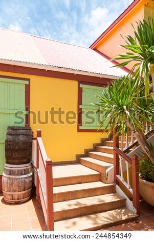 Barrels by steps outside an old colorful building in Philipsburg in St Martin - stock photo