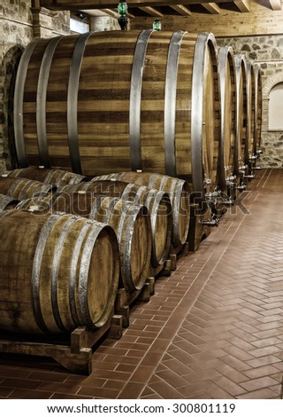 Barrels for storage of wine in the winery cellar - stock photo