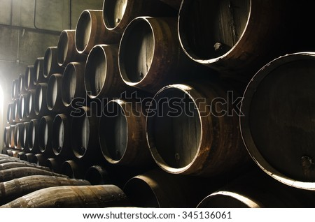 Barrels for whiskey or wine stacked in the cellar - stock photo