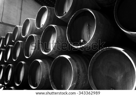 Barrels for whiskey or wine stacked in the cellar in black and white - stock photo