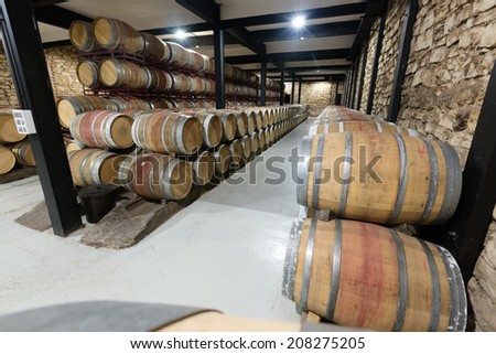 barrels in rows at contemporary winery - stock photo