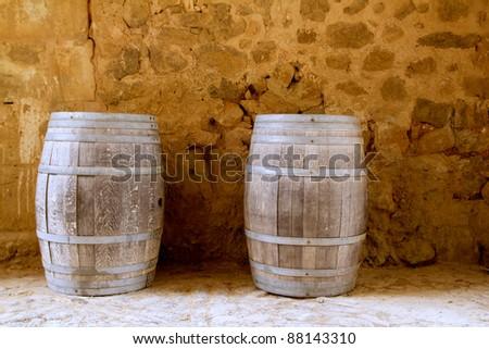 barrels of wine built in oak wood from Spain on stone masonry wall - stock photo