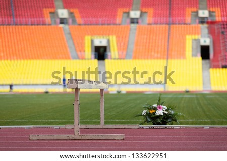 Barrier and beautiful flowers on the track stadium. - stock photo