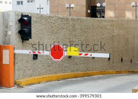 Barrier on parking lot with STOP sign - stock photo