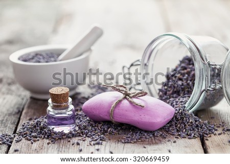 Bars of homemade soaps, dry lavender flowers and essential oil. Selective focus. - stock photo