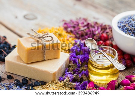 Bars of homemade soaps, honey or oil, heaps of healing herbs and mortar of lavender. Selective focus.  - stock photo
