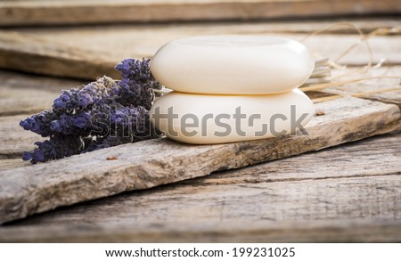 Bars of soap with lavender on a rustic wooden background - stock photo