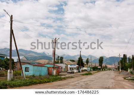 BARSKOON, KYRGYZSTAN - AUG 3: Small Central Asian town with one floor buildings and the mountains background on August 3, 2013. Kyrgyzstan's population is 5.4 million, 34% are younger age 15