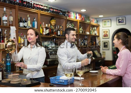 Bartender and positive barista working at bar. Focus on wairess - stock photo