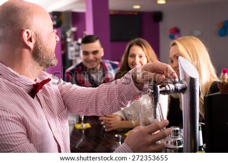 Bartender at a bar is pouring a beer from a tap and cheering up smiling visitors at a barstand - stock photo