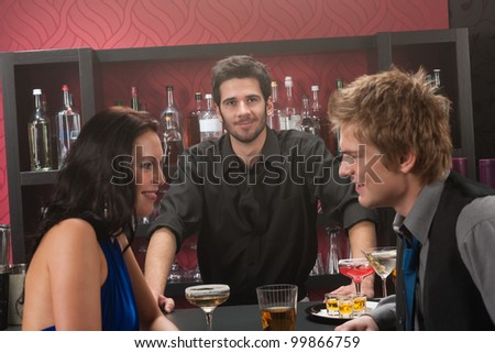 Bartender behind the bar couple having chat and drink - stock photo
