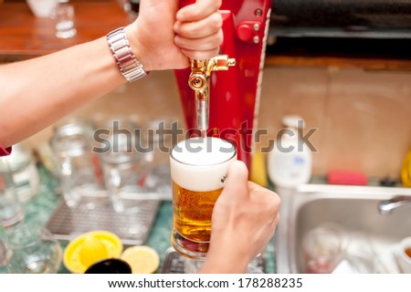 bartender brewing draft beer in pub - stock photo