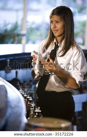 Bartender cleaning a wine glass - stock photo