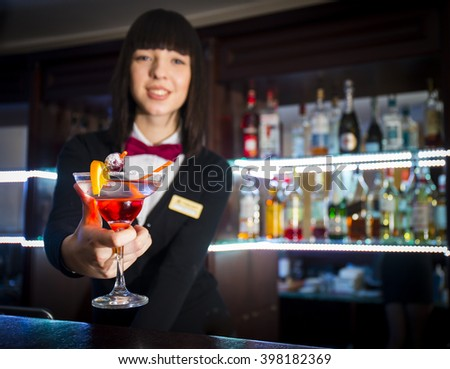 Bartender girl at night club counter offering coctail barmaid