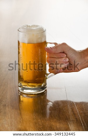 Bartender holding a freshly tapped glass of beer in his hand. - stock photo