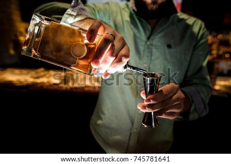 Bartender in shirt pouring a syrup for making an alcoholic cocktail on the background of bar