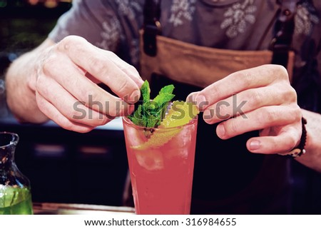 Bartender is adding mint to the cocktail at bar counter, toned image - stock photo
