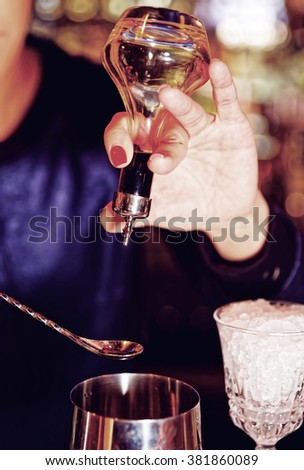 Bartender is adding some drops of bitter to shaker, toned - stock photo