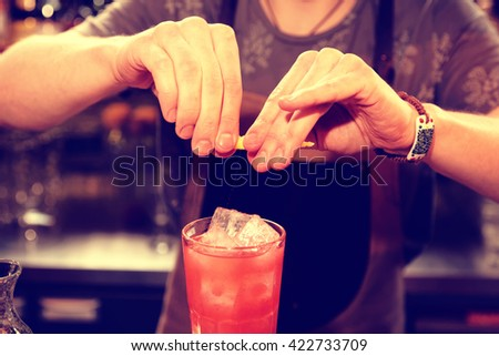 Bartender is adding zest oil to the cocktail, toned image - stock photo