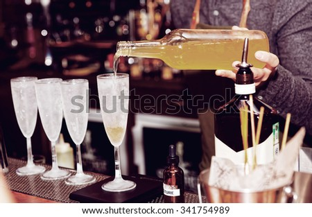 Bartender is pouring liquor in frozen glass - stock photo