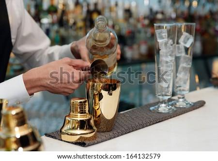 Bartender is pouring liquor in golden shaker - stock photo