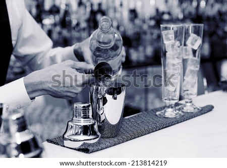 Bartender is pouring liquor in shaker, blue toned - stock photo