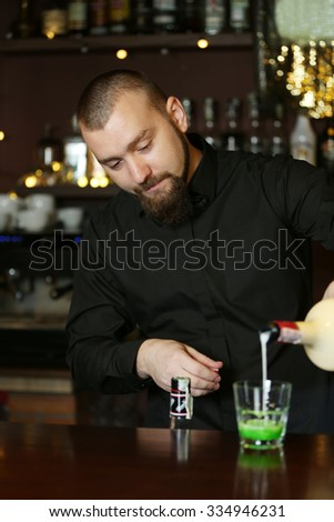 Bartender is pouring liquor into glass