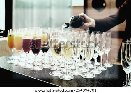 Bartender is pouring sparkling wine in glasses, making cocktails, toned image - stock photo