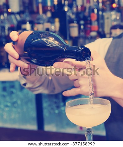 Bartender is pouring sparkling wine in the glass, toned image - stock photo