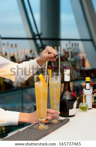 Bartender is stirring a cocktail in sling glass - stock photo