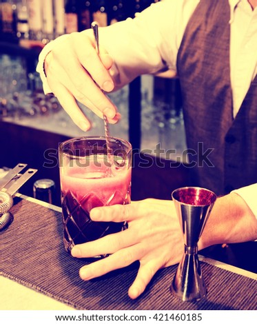 Bartender is stirring a shrub cocktail with sparkling wine, toned image - stock photo