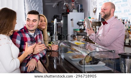 Bartender mixing cocktails for a company at the bar. Focus on barman - stock photo
