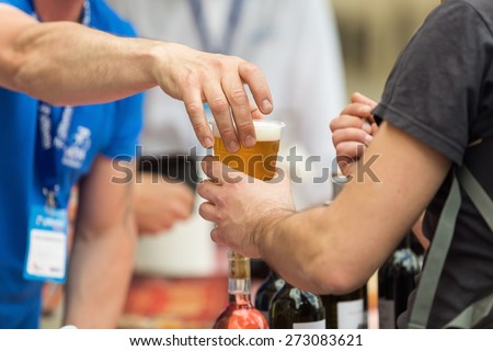 Bartender on the street bar handing a plastic glass of beer to a customer, holding the cup on top; during a street sporting event  - stock photo