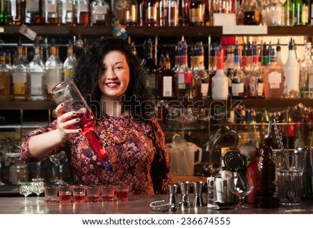 Bartender  pouring alcohol into shot glasses - stock photo