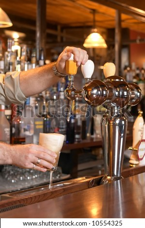 Bartender pouring beer from tap - stock photo
